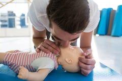 Bouche de pratique de ressuscitation d'infirmier à dire du bout des lèvres sur le simulacre Photographie stock