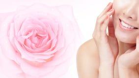 Bouche de sourire de jeune femme avec la fleur rose de rose Images libres de droits