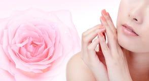 Bouche de sourire de jeune femme avec la fleur rose de rose Photos stock