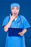 Bouche effrayée de revêtement d'infirmière avec la main Photo stock