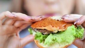 Bouche en gros plan de la belle fille affamée mangeant l'hamburger frais savoureux appréciant les aliments de préparation rapide clips vidéos