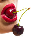 Bouche femelle avec des cerises Photo stock