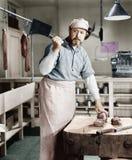 Boucher coupant la viande avec le fendoir (toutes les personnes représentées ne sont pas plus long vivantes et aucun domaine n'ex Photo libre de droits