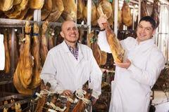 Boucher et assistant avec des joints de jamon Photographie stock libre de droits