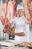Boucher Giving Raw Meat au compteur image stock