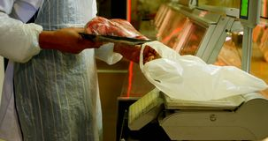 Boucher pesant la viande dans la boucherie 4k banque de vidéos