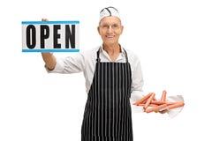 Boucher tenant des saucisses et un signe ouvert Image stock