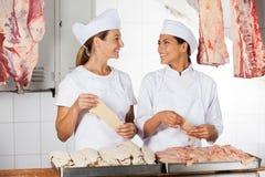 Bouchers féminins tenant la viande crue au compteur photos libres de droits