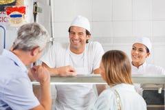Bouchers regardant le client dans la boutique Photos stock