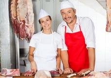 Bouchers sûrs se tenant au compteur dans la boucherie image stock