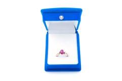 Boucle d'or avec le rubis dans le cadre de bijou bleu de velours Image stock