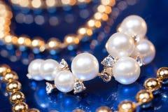 Boucle d'oreille de perle et programmes d'or Photographie stock libre de droits