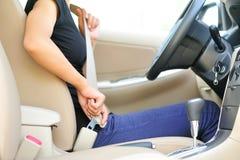 Boucle de conducteur de femme vers le haut de la ceinture de sécurité Photos libres de droits