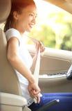 Boucle de conducteur de femme vers le haut de la ceinture de sécurité dans la voiture Photo libre de droits