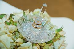 Boucle de mariage Deux anneaux de jeunes mariés de cru d'or et un support en cristal avec les roses blanches photo libre de droits