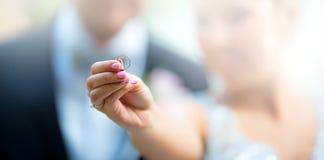 Boucle de mariage Jeunes mariés et anneau de mariage La jeune mariée avec le marié tient son anneau de mariage dans le premier pl Image libre de droits