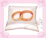 Boucles d'or de mariage sur l'oreiller de satin Photo stock