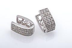 Boucles d'oreille argentées avec la macro photographie de cristaux sur Backgro blanc Photographie stock
