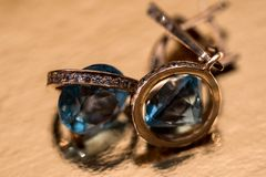 Boucles d'oreille d'or avec des cristaux sur le fond Photo stock