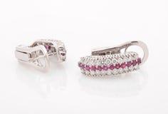 Boucles d'oreille avec des diamants sur le fond blanc Photos stock