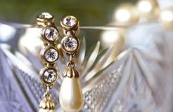 Boucles d'oreille d'or avec des perles et fausses pierres sur le verre cristal Photo libre de droits