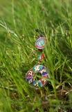 Boucles d'oreille avec le rubis sur l'herbe fraîche verte Photographie stock libre de droits
