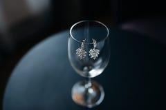 Boucles d'oreille d'accessoires de mariage sur le verre Image stock