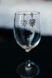 Boucles d'oreille d'accessoires de mariage sur le verre Photographie stock