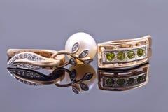 Boucles d'oreille d'or avec des émeraudes et avec la perle Photographie stock