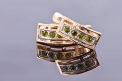 Boucles d'oreille d'or avec le mensonge vert et pendant sous forme de liza Image stock