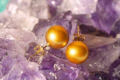 Boucles d'oreille d'or de perle sur le fond d'ametyst Images stock