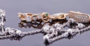 Boucles d'oreille d'or et chaîne argentée élégante Photos libres de droits