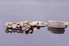 Boucles d'oreille d'or et chaîne argentée élégante Photographie stock libre de droits