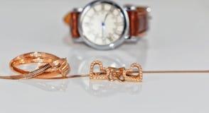 Boucles d'oreille d'or sous forme de coeur sur un fond d'élégant Photo libre de droits