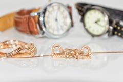 Boucles d'oreille d'or sous forme de coeur sur un fond d'élégant Photographie stock