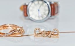 Boucles d'oreille d'or sous forme de coeur sur un fond d'élégant Image stock