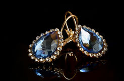Boucles d'oreille d'or sur un fond foncé photos stock