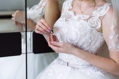 Boucles d'oreille dans les mains de la jeune mariée sur le fond noir Concept des bijoux Image libre de droits