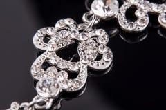 Boucles d'oreille de long argent cultivé ou d'or blanc avec des diamants et cristaux sur le fond réfléchi noir Macro photographie Images libres de droits