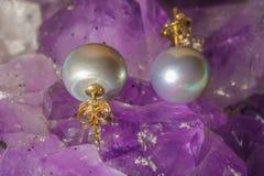 Boucles d'oreille de perle sur le fond d'ametyst Photographie stock