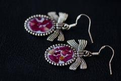 Boucles d'oreille de résine avec les pétales de rose secs sur un fond foncé Photo libre de droits