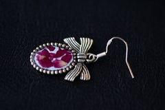 Boucles d'oreille de résine avec les pétales de rose secs sur un fond foncé Photo stock
