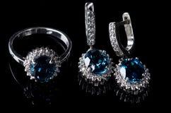 Boucles d'oreille et anneau du fond noir argenté Photos stock