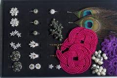 Boucles d'oreille et anneaux du ` s de femmes dans une boîte spéciale pour le stockage Une collection de bijoux pour différentes  Photos libres de droits