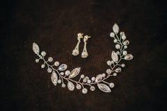 Boucles d'oreille et ornement précieux de cheveux dans les cheveux pour la jeune mariée Photo libre de droits