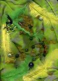 Boucles d'oreille et plumes avec le mensonge ambre sur le fond vert de textile Photos stock