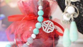 Boucles d'oreille et un collier de vase à bleu et à blanc de turquoise sur une belle couleur rouge banque de vidéos