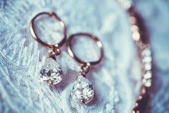 Boucles d'oreille sur la robe de mariage blanche Photos libres de droits