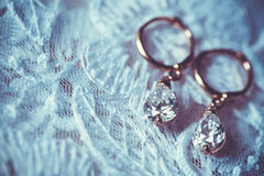 Boucles d'oreille sur la robe de mariage blanche Images stock