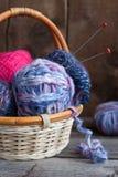 Boucles de laine pour tricoter avec des pointeaux de tricotage dans un panier Photo libre de droits